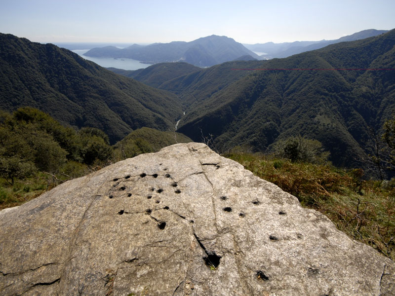 Boulder with cup and ring marks and Maggiore Lake in the background